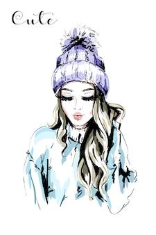 Bella giovane donna in cappello lavorato a maglia con pom-pom di pelliccia