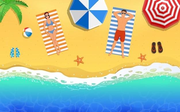 Bella giovane donna e uomo che prendono il sole sulla spiaggia