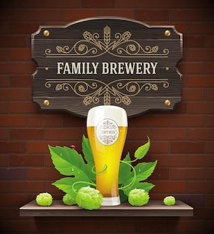 Birra vintage cartello bicchiere di birra e hop su uno sfondo di muro di mattoni