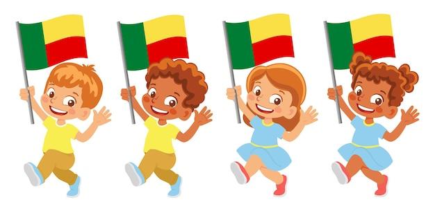 Bandiera del benin in mano. bambini che tengono bandiera. bandiera nazionale del benin