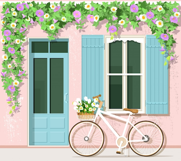 Bicicletta con fiori vicino alla casa in stile provenzale