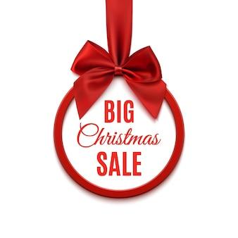 Grande vendita di natale, banner rotondo con nastro rosso e fiocco, isolato su sfondo bianco.