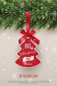 Grande modello di vendita di natale, albero di capodanno con etichetta rossa con nastro.