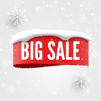 Grande insegna di vendita con il cappuccio rosso della neve dell'etichetta e fiocchi di neve