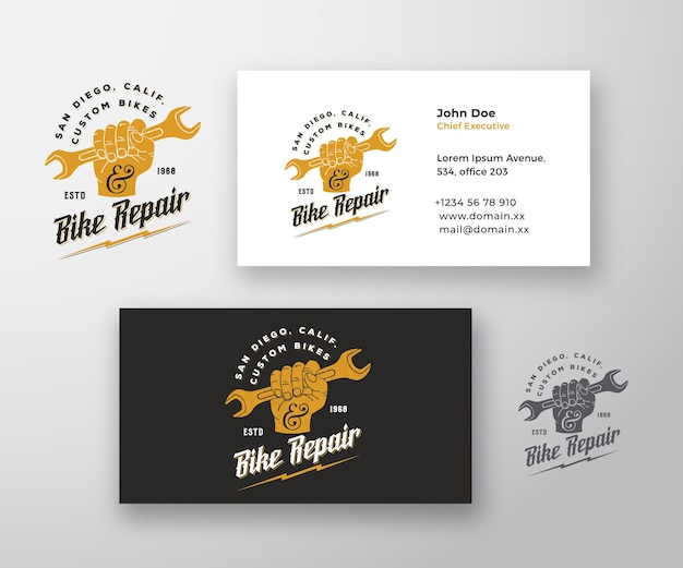 Riparazione bici astratto moderno vettore logo e modello di biglietto da visita pugno tenendo la chiave con retro ty...
