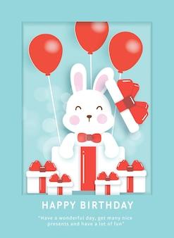 Modello di carta di compleanno con coniglio carino in una confezione regalo.