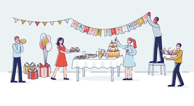 Preparazione della festa di compleanno con persone che decorano la stanza e la tavola delle vacanze con la torta.