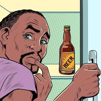 Un uomo afroamericano nero vicino al frigorifero con la birra dipendenza da alcol