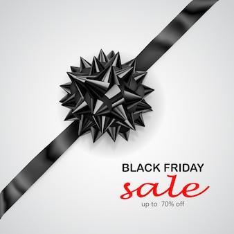 Fiocco nero con nastro diagonalmente con ombra e scritta black friday sale su sfondo bianco