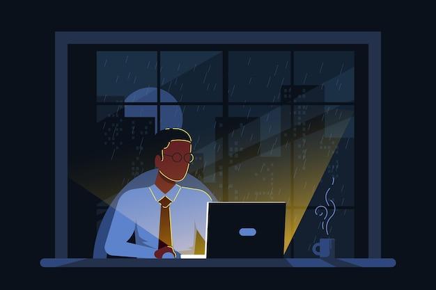 Uomo d'affari nero che lavora al computer alla scrivania in ufficio nella notte.
