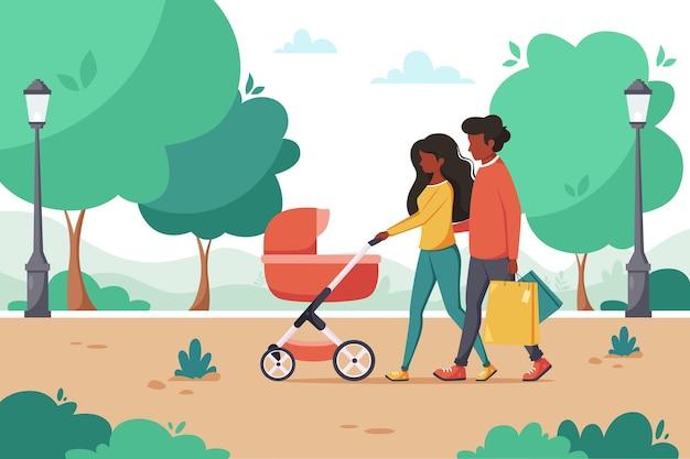 Famiglia nera con carrozzina che cammina nel parco. attività all'aperto