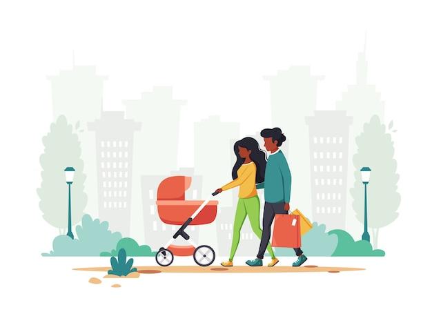 Famiglia nera con carrozzina che cammina nel parco.