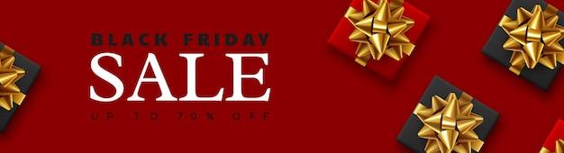 Banner di vendita del black friday. confezione regalo realistica con fiocco dorato. sfondo rosso. illustrazione vettoriale.