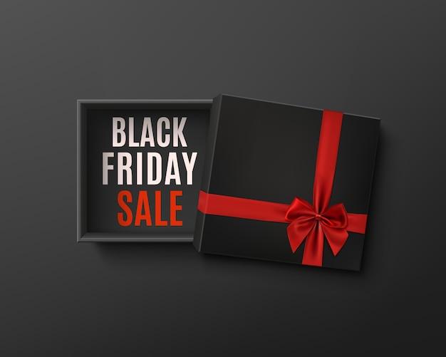 Progettazione di vendita del black friday. contenitore di regalo vuoto nero aperto con nastro rosso e fiocco su sfondo scuro. vista dall'alto. modello per il design della presentazione, banner, brochure o poster.