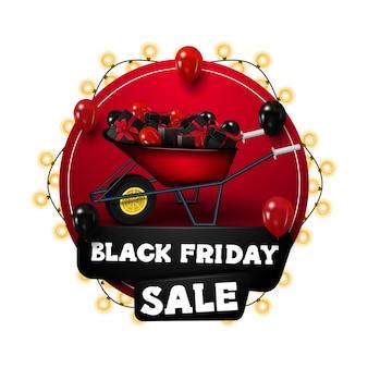 Vendita venerdì nero, banner sconto cerchio rosso avvolto con ghirlande, decorato con carriola con regali e palloncini. banner di sconto isolato