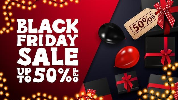 Saldi del black friday, fino al 50% di sconto, banner sconto rosso e blu con regali neri, cornice ghirlanda e palloncini rossi e neri, vista dall'alto.