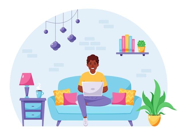 Uomo nero seduto su un divano e lavora al computer portatile