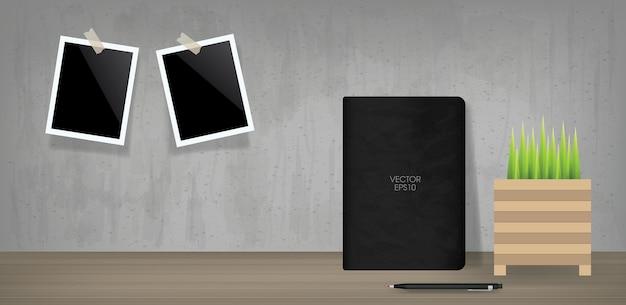 Taccuino nero e cornice per foto in bianco nella priorità bassa dello spazio della camera dell'annata