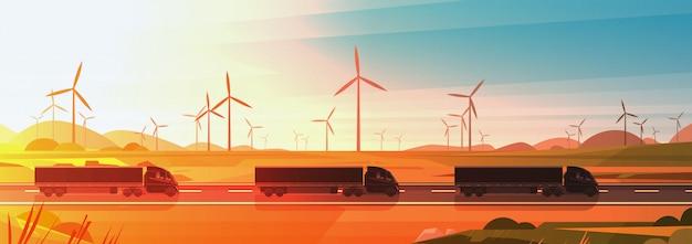 Rimorchi neri del camion dei semi che guidano strada in insegna orizzontale del paesaggio del tramonto della natura della campagna