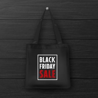 Borsa tote in tessuto nero con la scritta black friday sale primo piano su parete nera in legno