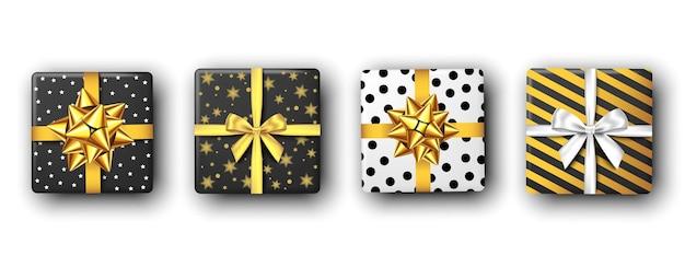 Confezione regalo in bianco e nero con nastro e fiocco argento e dorato, vista dall'alto