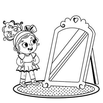 La bambina in bianco e nero prova gli abiti guardando lo specchio