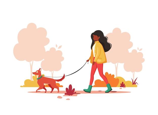 Donna nera che cammina con il cane nel parco in autunno. concetto di attività all'aperto.