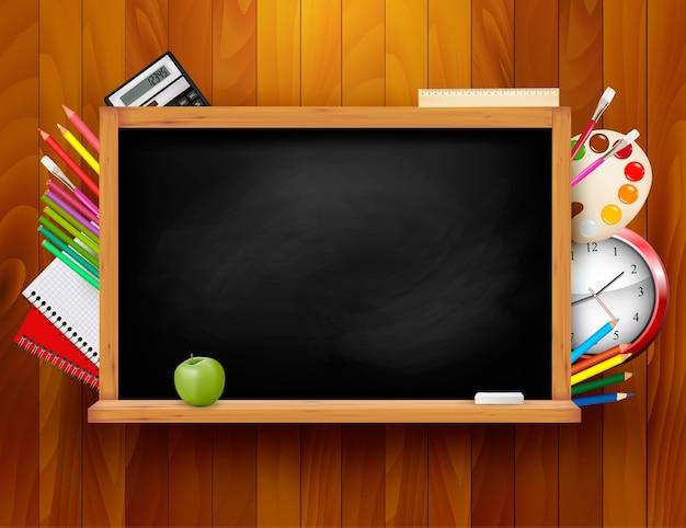 Lavagna con materiale scolastico su sfondo di legno