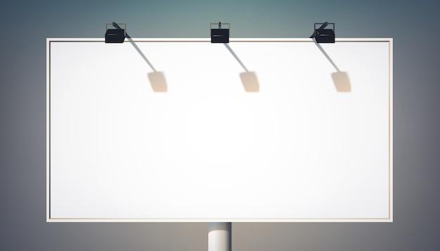 Tabellone per le affissioni orizzontale commerciale in bianco sulla colonna metallica per la pubblicità e la promozione con i riflettori isolati
