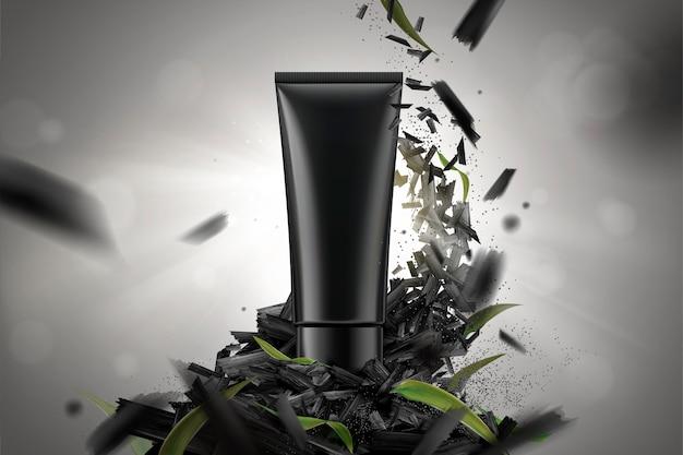 Vuoto tubo di plastica cosmetica con carboni frantumati e foglie su sfondo bokeh di fondo