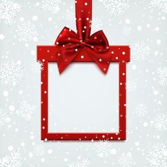 Striscione quadrato rosso vuoto a forma di regalo di natale con nastro rosso e fiocco, su sfondo invernale con neve e fiocchi di neve. brochure o modello di banner.