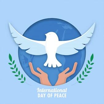 Carta blu tagliata a forma di cerchio globo terrestre sfondo con mani che rilasciano colomba e rami di foglie di ulivo verde per la giornata internazionale della pace.