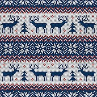 Modello senza cuciture a maglia blu e rosso con cervi e ornamento scandinavo tradizionale.