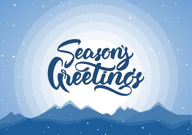 . sfondo blu montagne invernali con scritte a mano di auguri di buone feste.