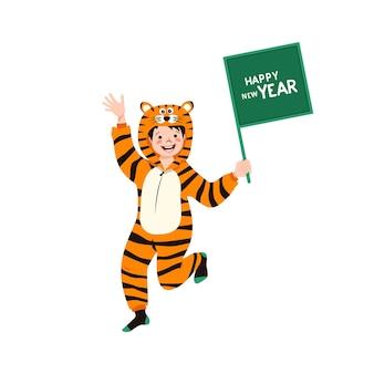 Ragazzo in costume di carnevale di tigre cinese con segno per il testo in mano bambino in pigiama da festa bambino in ju...