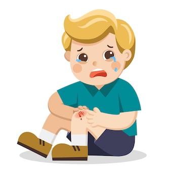 Un ragazzo che tiene graffio doloroso del ginocchio della gamba ferita