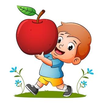 Il ragazzo tiene in mano la mela rossa matura con la felice espressione dell'illustrazione
