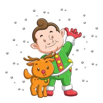 Ragazzo in piedi sotto la neve e usando il cappotto verde caro il suo cane