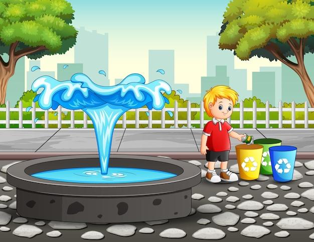 Il ragazzo getta i rifiuti di plastica nel bidone della spazzatura nel parco