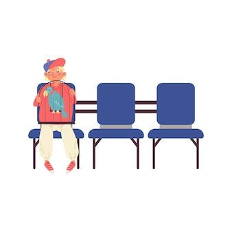 Ragazzo con pappagallo seduto in clinica veterinaria in attesa di appuntamento dal medico veterinario