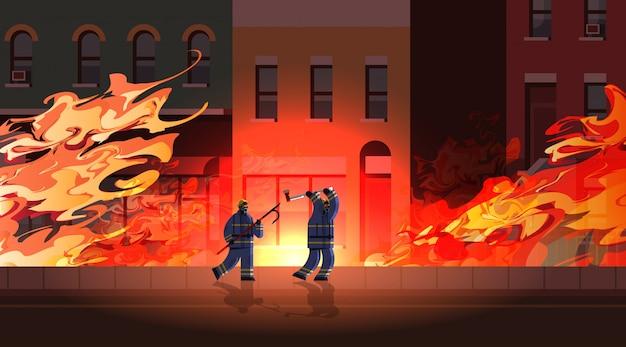 Fuochi d'artificio coraggiosi utilizzando rottami e ascia pompieri in uniforme antincendio servizio di emergenza estinzione incendio concetto arancia fiamma ardente edificio esterno integrale lunghezza orizzontale