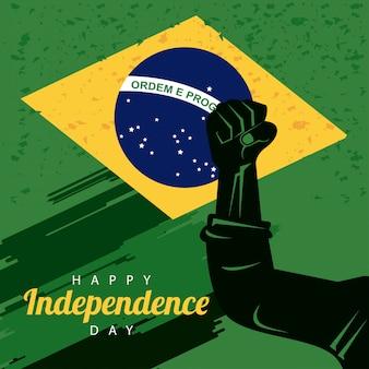 Celebrazione felice del giorno dell'indipendenza del brasile con bandiera e pugno di mano