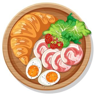 Croissant della prima colazione con il prosciutto e l'uovo sodo su un piatto isolato
