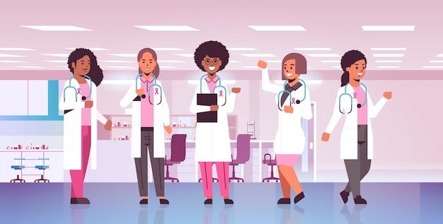 Medici del giorno del cancro al seno che indossano cappotti con il gruppo rosa dei colleghi dell'ospedale della corsa della miscela del nastro che stanno insieme orizzontale integrale integrale di concetto di consapevolezza e di prevenzione della malattia