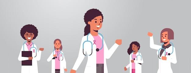 Medici del giorno del cancro al seno che indossano cappotti con il gruppo rosa dei colleghi dell'ospedale della corsa della miscela del nastro che stanno insieme orizzontale piano del ritratto di concetto di consapevolezza e di prevenzione di malattia