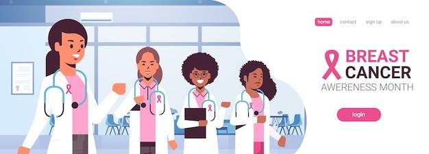 Medici del giorno del cancro al seno che indossano cappotti con nastro rosa mix gara squadra di colleghi ospedalieri in piedi insieme consapevolezza e prevenzione della malattia