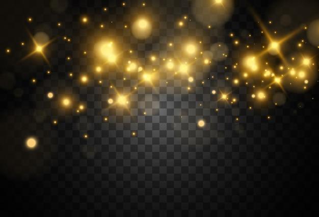 Scintille dorate belle luminose su uno sfondo trasparente.