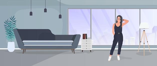 Ragazza bruna in posa. modello in un abito elegante. camera, divano, lampada da terra, quadri alle pareti, libreria con libri, una ragazza con i capelli neri. .