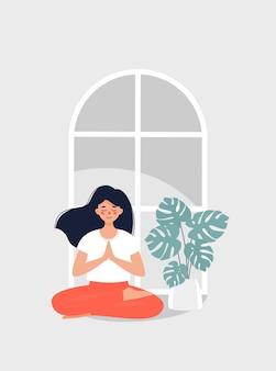Donna castana che si siede nella posizione di loto dalla finestra e dai monstera in vaso
