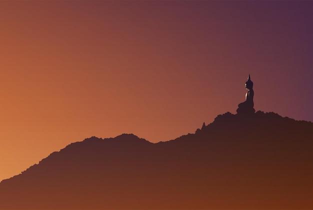 Una statua di buddha in posizione seduta sulla vetta della montagna